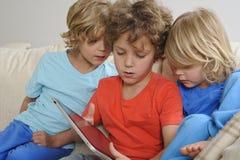 Três meninos com tabuleta foto de stock