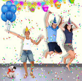 Três meninos e um cão estão tendo o divertimento em um partido Imagens de Stock Royalty Free