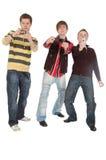 Três meninos que disparam em algo no telefone móvel imagem de stock