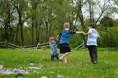 Três meninos que guardam a corrida das mãos imagens de stock
