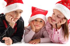Três miúdos nos tampões do Natal Fotografia de Stock