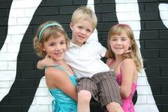 Três miúdos por uma parede da zebra Fotografia de Stock Royalty Free