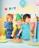Três miúdos que comem o bolo na festa de anos Imagem de Stock