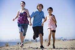 Três miúdos que funcionam na praia Foto de Stock Royalty Free