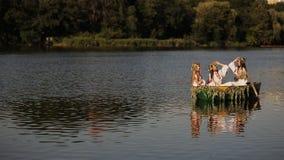 Três moças com cabelo longo em um barco que flutua no rio Meninas em trajes eslavos com uma grinalda em sua cabeça vídeos de arquivo