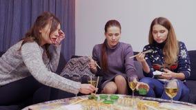 Três moças comem o sushi em casa vídeos de arquivo