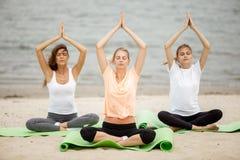 Três moças delgadas sentam-se em uma ioga levantam com os olhos de fechamento em esteiras no Sandy Beach em um dia morno imagens de stock royalty free