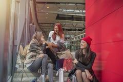 Três moças encantadores que falam no shopping imagens de stock royalty free