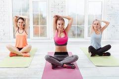 Três moças que fazem exercícios da ioga foto de stock