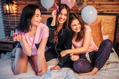 Três modelos novos que sentam-se na cama na sala e no jogo Guardam flores nas mãos Menina no direito que inclina-se à menina dent imagens de stock