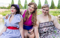Três modelos positivos do tamanho estão sentando-se no lago Fotos de Stock