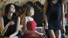 Três modelos sedutores nos vestidos de noite que levantam na cama 4K video estoque