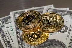 Três moedas do bitcoin do ouro e dólares americanos do close-up fotografia de stock royalty free