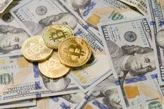 Três moedas simbólicas do bitcoin em cédulas de cem dólares Dinheiro do bitcoin da troca para um dólar Foto de Stock Royalty Free