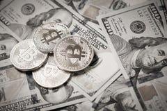 Três moedas simbólicas do bitcoin em cédulas de cem dólares Dinheiro do bitcoin da troca para um dólar Fotos de Stock Royalty Free