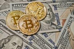 Três moedas simbólicas do bitcoin em cédulas de cem dólares Dinheiro do bitcoin da troca para um dólar Foto de Stock