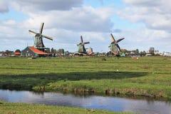Três moinhos de vento em um prado, entre os canais profundos fotografia de stock royalty free
