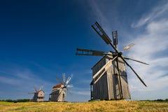 Três moinhos de vento tradicionais no campo no por do sol Imagem de Stock