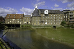 Três moinhos e moinhos da casa com pasto do rio no primeiro plano Fotografia de Stock Royalty Free