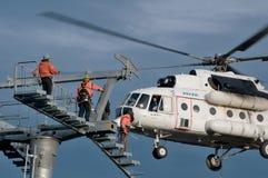 Três montadores batendo sob o helicóptero Fotografia de Stock Royalty Free