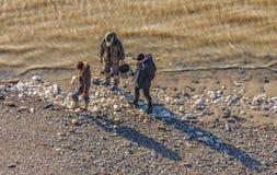 Três mudlarks que procuram ao longo do foreshore do rio Tamisa fotografia de stock royalty free