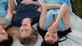 Três mulheres atrativas novas estão encontrando-se em uma manta e estão olhando-se o céu Riso e ponto acima, dança Amigas do rest video estoque
