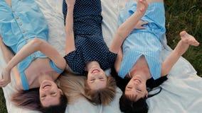 Três mulheres atrativas novas estão encontrando-se em uma manta e estão olhando-se o céu Riso e ponto acima, dança Amigas do rest vídeos de arquivo