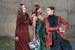 Três mulheres bonitas que falam o estilo da rua da forma foto de stock