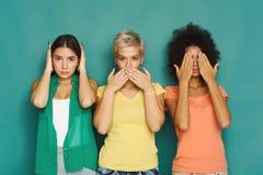 Três mulheres bonitas que levantam no fundo verde Fotos de Stock Royalty Free