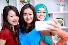 Três mulheres bonitas que tomam fotos com câmera do smartphone foto de stock