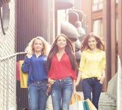 Três mulheres bonitas que vão abaixo das escadas da rua após a compra Fotos de Stock Royalty Free