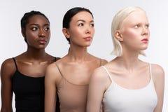 Três mulheres com os camisoles vestindo da cor da pele diferente fotografia de stock royalty free