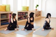 Três mulheres da morena que têm o tempo em classes da ioga, flexibilidade praticando na ioga que senta o meio senhor dos peixes l imagem de stock royalty free