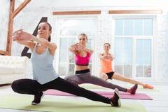 Três mulheres deleitadas que fazem a aptidão exercitam junto imagens de stock