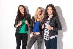 Três mulheres felizes no sorriso dos casacos de cabedal Imagem de Stock