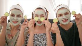 Três mulheres felizes novas com máscaraes protetoras que passam o tempo no spa resort Amizade e conceito do bem estar, beleza da  video estoque