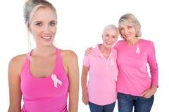 Três mulheres felizes que vestem partes superiores e fitas cor-de-rosa do câncer da mama Fotografia de Stock Royalty Free