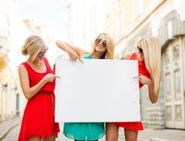 Três mulheres louras felizes com placa branca vazia imagem de stock royalty free