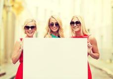 Três mulheres louras felizes com placa branca vazia Fotos de Stock