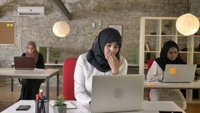 Três mulheres muçulmanas novas no hijab que senta-se e que trabalha no portátil no escritório moderno, bocejo muçulmano da mulher filme