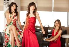 Três mulheres novas bonitas em um piano Fotos de Stock