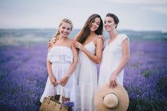 Três mulheres que levantam em um campo da alfazema Fotos de Stock Royalty Free