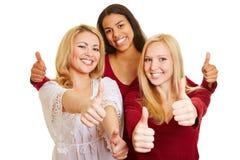Três mulheres que mantêm os polegares foto de stock royalty free