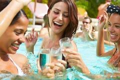 Três mulheres que têm o partido na piscina que bebe Champagne Foto de Stock