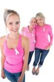 Três mulheres que vestem partes superiores e fitas cor-de-rosa do câncer da mama Imagens de Stock Royalty Free