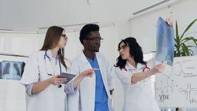 Três multi doutores nacionais que discutem o raio X dos pulmões do paciente durante o dia do trabalho video estoque