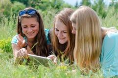 Três namoradas e tablet pc adolescentes felizes Fotografia de Stock