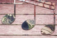 Três notas do metal na parede de tijolo Fotos de Stock Royalty Free