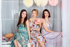Três novos, meninas bonitas e atrativas no Dr. colorido brilhante Imagem de Stock