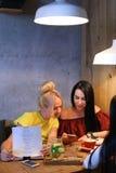 Três o sorriso fêmea bonito no café, conversa, diz segredos, come, d Imagens de Stock Royalty Free